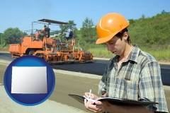 wyoming map icon and a civil engineer inspecting a road building project